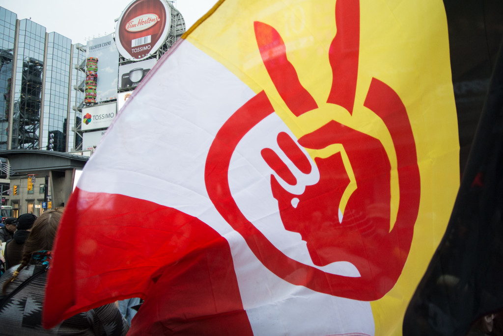 A demonstrator waves a flag during an Idle No More protest on January 11, 2013 at Yonge Dundas Square in Toronto.