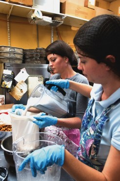 Kiley McLean (right) and her sister Cara (left) pour freshly made almond milk into the strainer bag for filtering. –James Sturrock (photo)