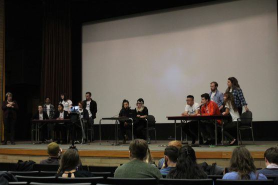 Candidates stand on stage responding to audience questions at the UVSS Election debates