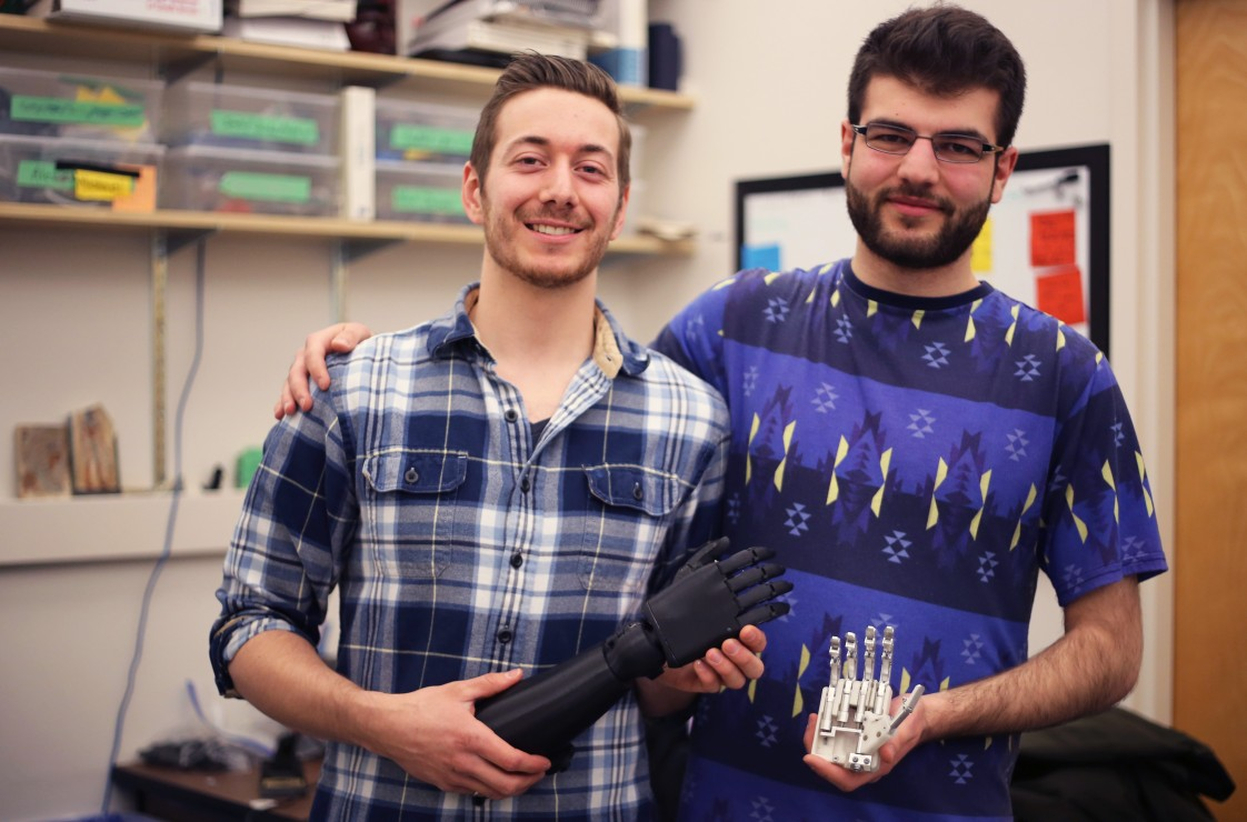 Victoria Hand Project workers Michael Peirone and Sina Valizadeh pose with various prosthetic models.