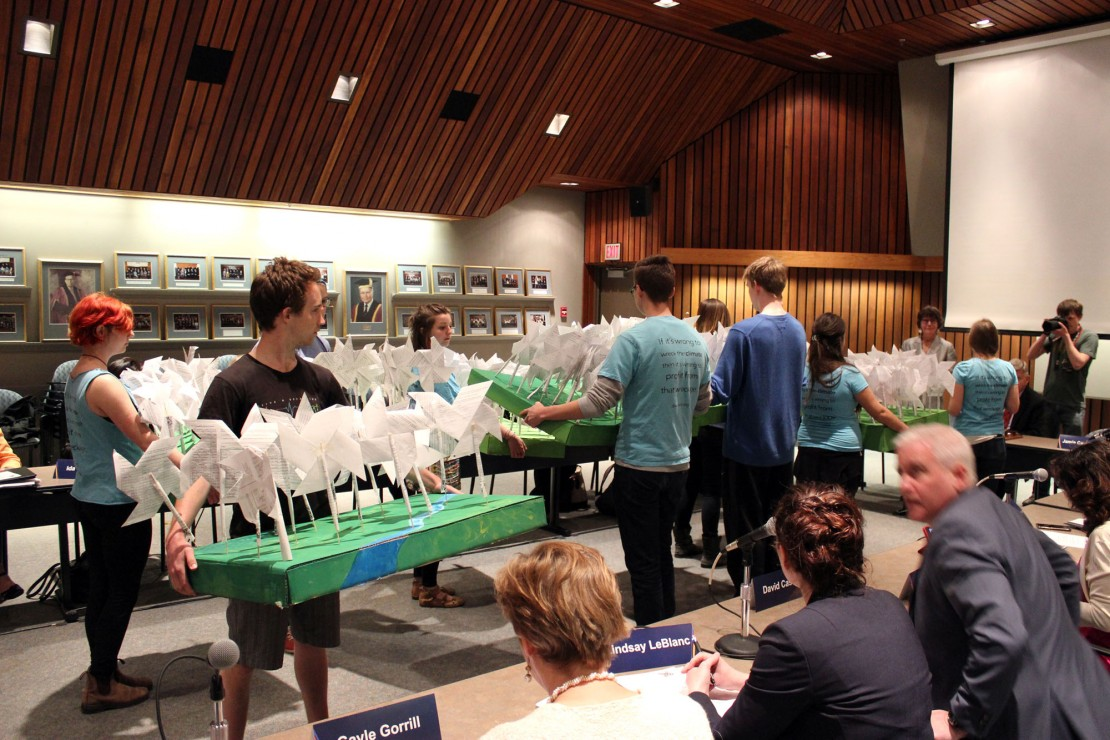 Divest UVic presents the Board of Governors with over 200 handmade wind turbines made from student petitions. Photo by Myles Sauer