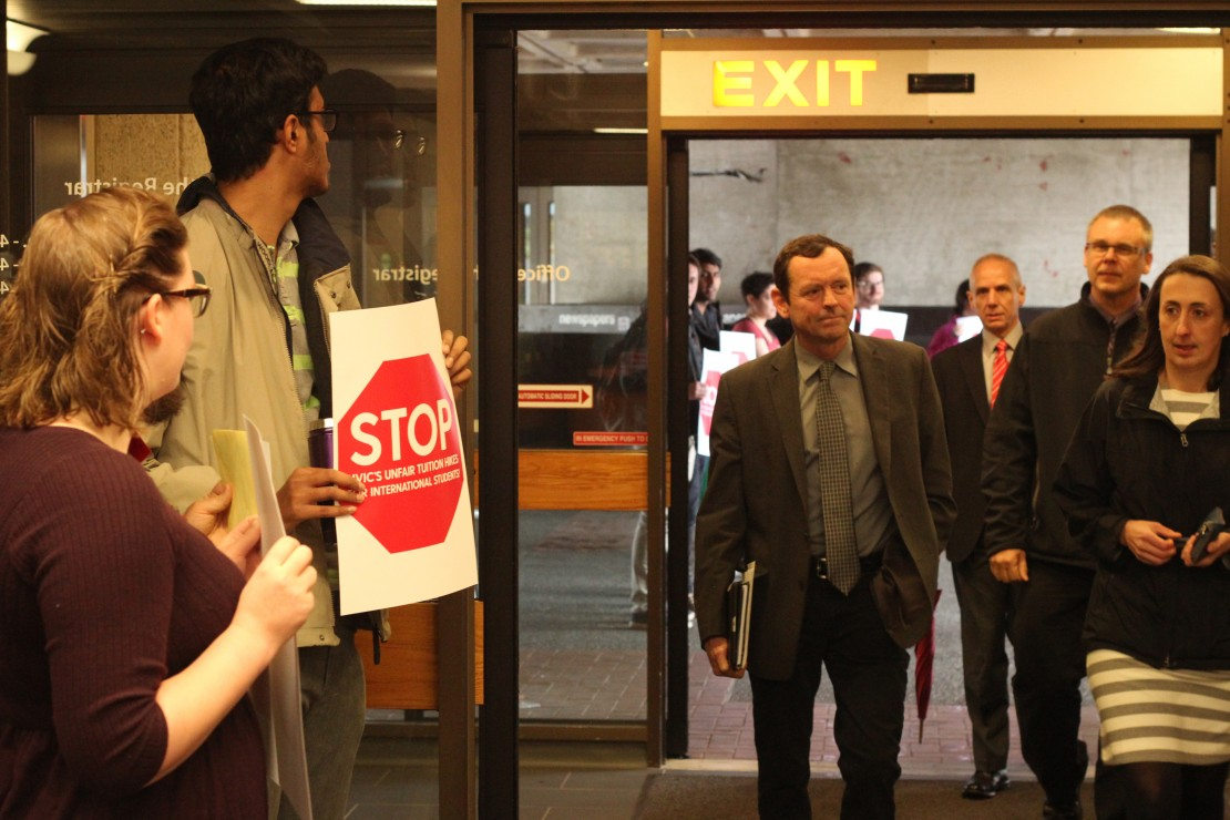 UVic President Jamie Cassels heads into the Board of Governors meeting Tuesday morning as protesters stand by with signs. The board voted in favour of implementing a four per cent increase to international student fees. Photo by Myles Sauer, Editor-in-Chief