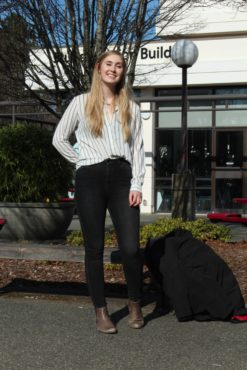 Ainsley Kerr, Candidate for Campaigns and Community Relations with Envision UVic, stands in front of the SUB wearing a striped top and black jeans.