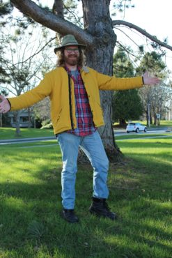 Dirk Slot pictured wearing a hat, yellow coat, plaid shirt, and jeans. He is a UVSS candidate for director for student affairs.
