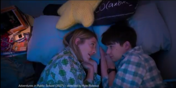 A mother and son lay next to each other talking in the trailer for the film Adventures in Public School